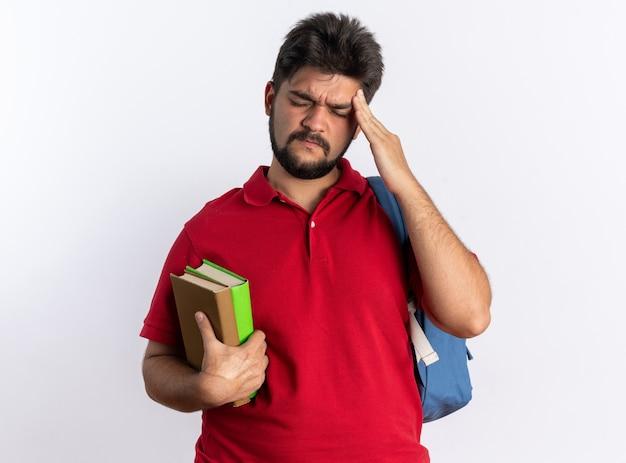 Jonge, bebaarde student in een rood poloshirt met rugzak met notitieboekjes die er niet goed uitziet terwijl hij zijn slaap aanraakt, pijn voelt die over een witte muur staat