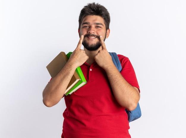 Jonge, bebaarde student in een rood poloshirt met rugzak met notitieboekjes die met de vingers naar zijn grote glimlach wijzen die over een witte muur staat