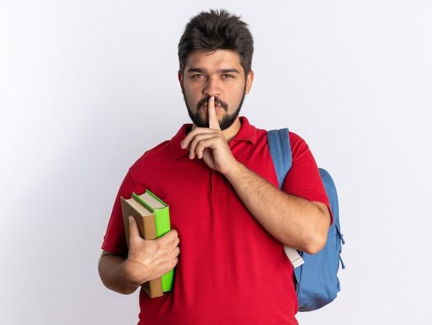 Jonge, bebaarde student in een rood poloshirt met rugzak met notitieboekjes die op zoek is naar stiltegebaar met de vinger op de lippen staand