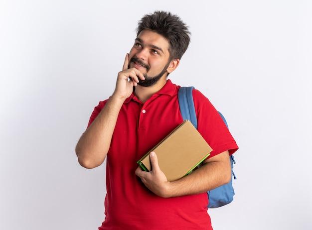 Jonge, bebaarde student in een rood poloshirt met rugzak met notitieboekjes die opkijkt met een glimlach op het gezicht, positief denkend over een witte muur