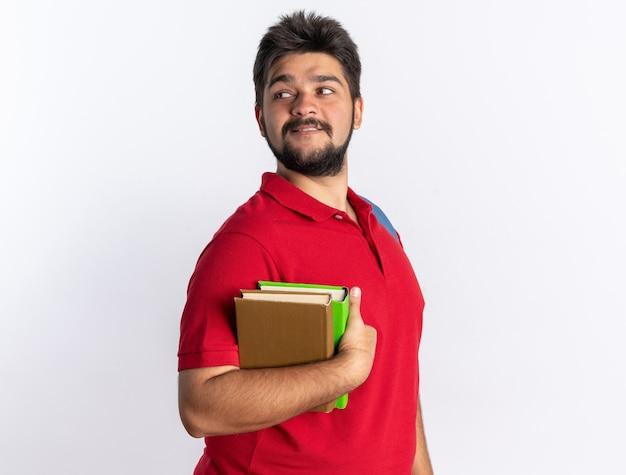 Jonge, bebaarde student in een rood poloshirt met rugzak met notitieboekjes die opzij kijkt en glimlachend zelfverzekerd over een witte muur staat