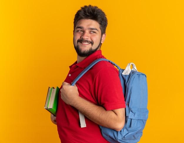 Jonge, bebaarde student in een rood poloshirt met rugzak met notitieboekjes die opzij kijkt glimlachend zelfverzekerd, gelukkig en positief over de oranje muur