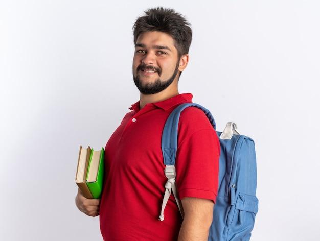 Jonge, bebaarde student in een rood poloshirt met rugzak met notitieboekjes glimlachend zelfverzekerd, gelukkig en positief over een witte muur