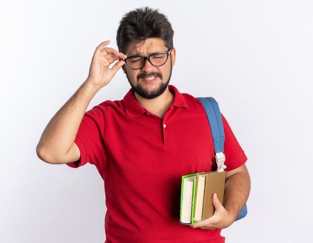Jonge, bebaarde student in een rood poloshirt met rugzak met notitieboekjes met een bril die blij en vrolijk over een witte muur staat