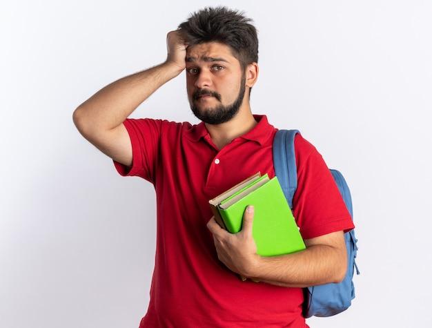 Jonge, bebaarde student in een rood poloshirt met rugzak met notitieboekjes verward met de hand op zijn hoofd voor een fout die over een witte muur staat