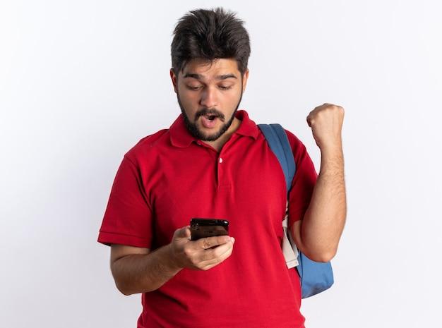 Jonge, bebaarde student in een rood poloshirt met rugzak met smartphone die er blij en verrast naar kijkt