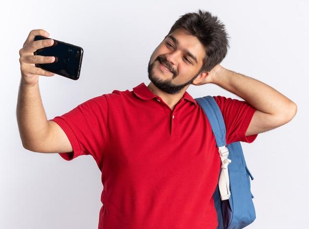 Jonge, bebaarde student in een rood poloshirt met rugzak met smartphone die selfie maakt, vrolijk en vrolijk glimlacht