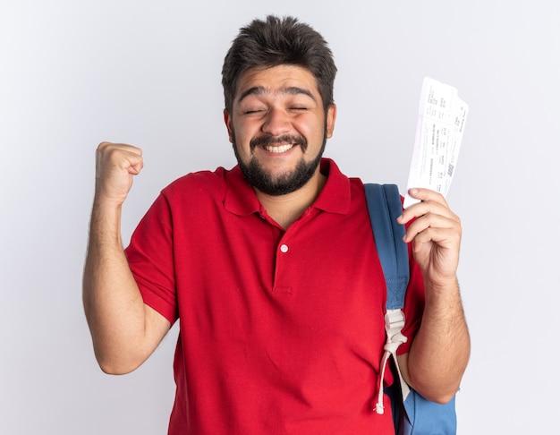 Jonge, bebaarde student in een rood poloshirt met rugzak met vliegtickets, blij en opgewonden, gebalde vuist staand