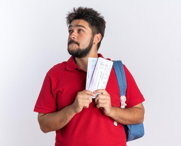 Jonge, bebaarde student in een rood poloshirt met rugzak met vliegtickets die opkijkt met een glimlach op het gezicht en een positieve status denkt
