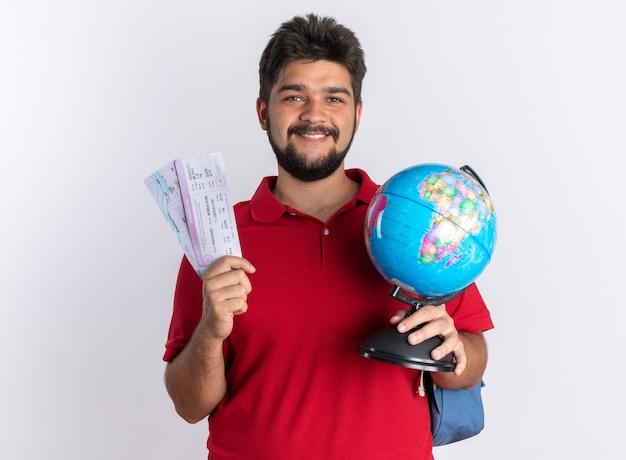 Jonge, bebaarde student in een rood poloshirt met rugzak met vliegtickets en een wereldbol die blij en positief glimlachend staat