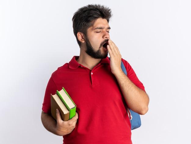 Jonge, bebaarde student in rood poloshirt met rugzak met notebooks die er moe uitziet, wil slapen geeuwen staande over witte muur