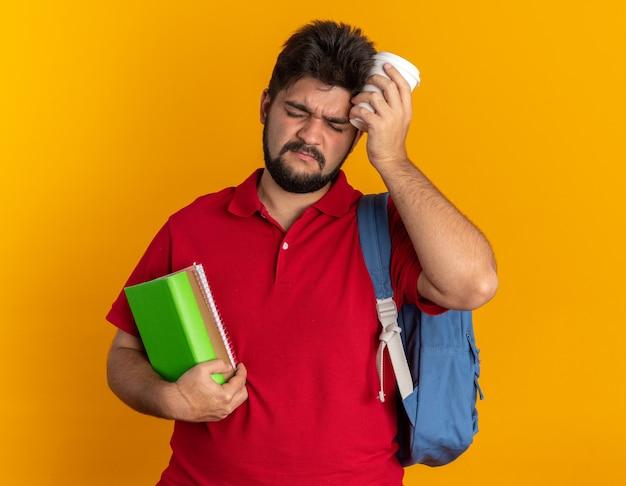 Jonge, bebaarde student man in rood poloshirt met rugzak bedrijf notebooks en papieren beker op zoek moe en overwerkt staande over oranje achtergrond