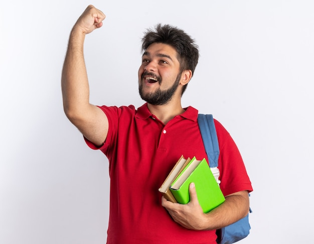 Jonge, bebaarde student man in rood poloshirt met rugzak met notebooks balde vuist blij en opgewonden blij met zijn succes staande over witte muur