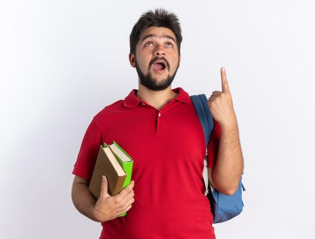 Jonge, bebaarde student man in rood poloshirt met rugzak met notebooks opzoeken blij en opgewonden wijzend met wijsvinger omhoog staande over witte muur