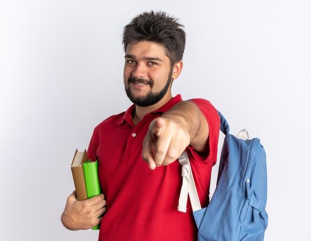 Jonge, bebaarde student man in rood poloshirt met rugzak met notebooks wijzend met wijsvinger glimlachend vrolijk gelukkig en positief staande over witte muur