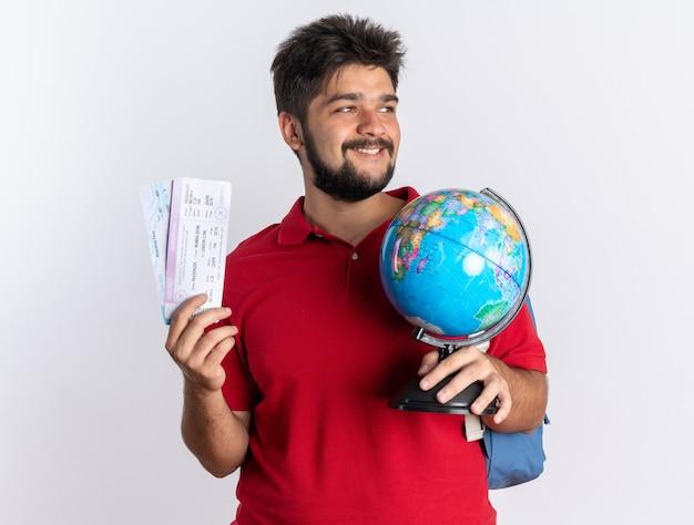 Jonge, bebaarde student man in rood poloshirt met rugzak met vliegtickets en globe opzij kijkend met glimlach op blij gezicht staande over witte muur