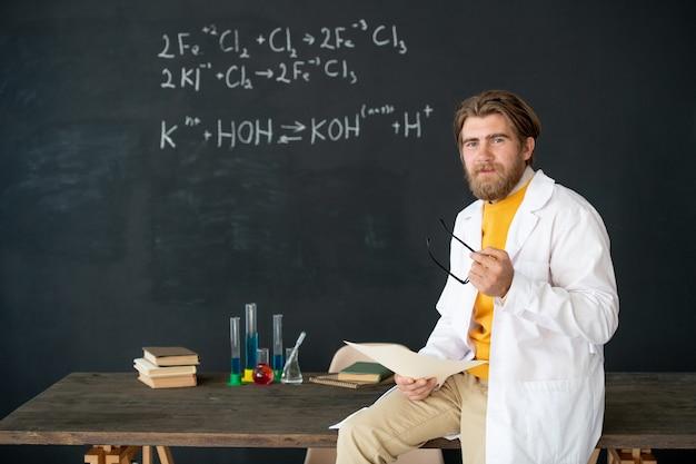 Jonge, bebaarde succesvolle leraar scheikunde houden brillen en papieren zittend op tafel voor camera tijdens online les