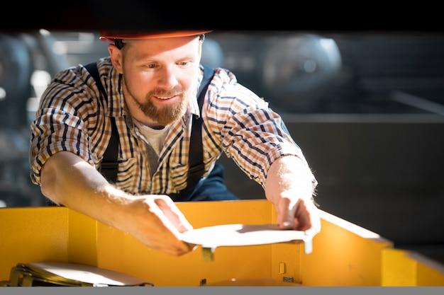 Jonge, bebaarde technicus in werkkleding en helm bukken mechanisme van industriële machine in fabriek