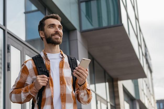 Jonge, bebaarde toerist die met rugzak op stedelijke straat loopt, beste manier zoekt. reis concept