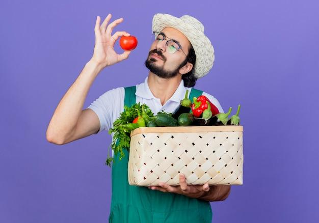Jonge, bebaarde tuinman die een jumpsuit en een hoed draagt en een krat vol groenten en verse tomaat houdt die ernaar kijkt geïntrigeerd staande over de blauwe muur