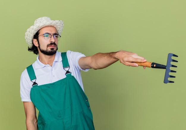 Jonge, bebaarde tuinman die een jumpsuit en een hoed draagt en een mini-hark houdt die naar de kant wijst en met een ernstig gezicht over de lichtgroene muur kijkt
