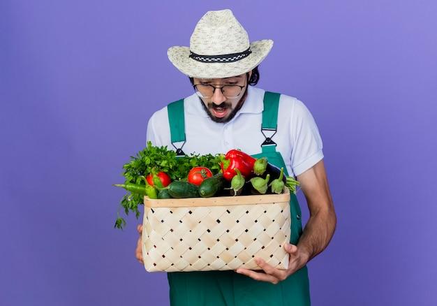 Jonge, bebaarde tuinman man met jumpsuit en hoed bedrijf krat vol groenten kijken verbaasd en verbaasd staande over blauwe muur