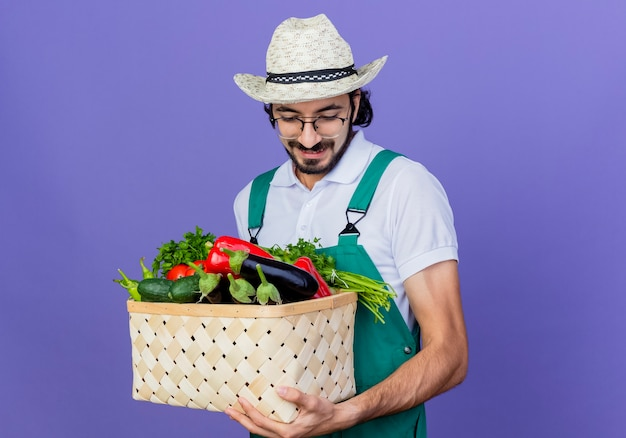 Jonge, bebaarde tuinman man met jumpsuit en hoed bedrijf krat vol groenten naar beneden glimlachend staande over blauwe muur