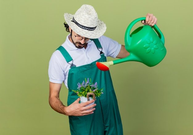 Jonge, bebaarde tuinman man met jumpsuit en hoed met gieter en potplant drenken staande over lichtgroene muur