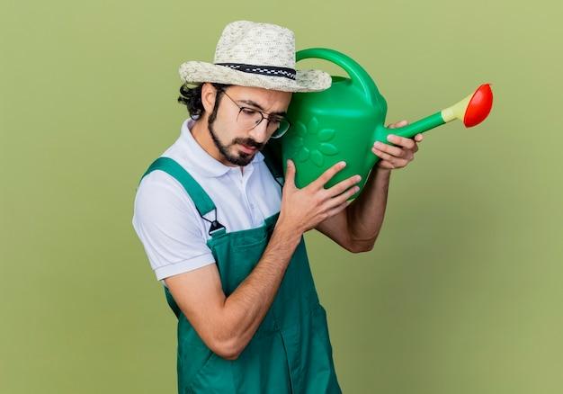Jonge, bebaarde tuinman man met jumpsuit en hoed met gieter opzij kijken verbaasd staande over lichtgroene muur