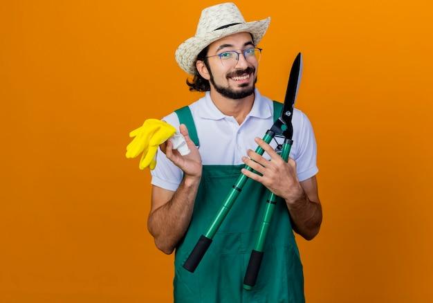 Jonge, bebaarde tuinman man met jumpsuit en hoed met heggenschaar en rubberen handschoenen kijken naar voorkant glimlachend vrolijk staande over oranje muur