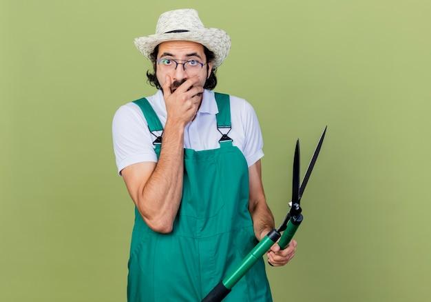 Jonge, bebaarde tuinman man met jumpsuit en hoed met heggenschaar op zoek verrast en verbaasd staande over de lichtgroene muur