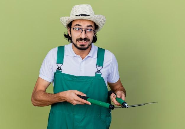 Jonge, bebaarde tuinman man met jumpsuit en hoed met heggenschaar opzij kijken verward staande over lichtgroene muur