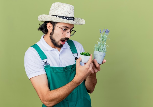 Jonge, bebaarde tuinman man met jumpsuit en hoed met potplanten kijken naar hen verrast staande over de lichtgroene muur