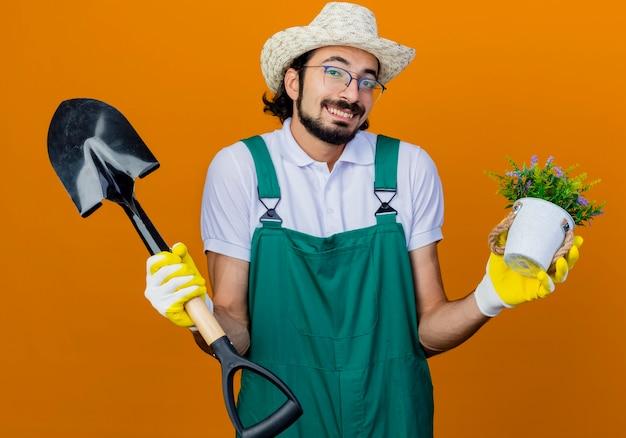 Jonge, bebaarde tuinman man met jumpsuit en hoed met schop en potplant op zoek verward schouderophalend