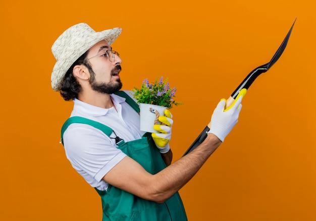 Jonge, bebaarde tuinman man met jumpsuit en hoed met schop en potplant opzij kijken met arm uit staande over oranje muur