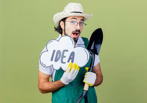 Jonge, bebaarde tuinman man met jumpsuit en hoed met schop en tekstballon bord met woord idee blij en opgewonden staande over lichtgroene muur