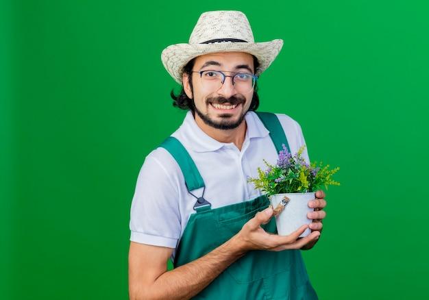 Jonge, bebaarde tuinman met een jumpsuit en een hoed die een potplant vasthoudt en er glimlachend uitziet met een blij gezicht over een groene achtergrond