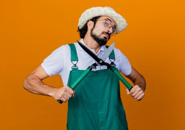 Jonge, bebaarde tuinman met een jumpsuit en een hoed met een heggenschaar die verward en verbaasd staat