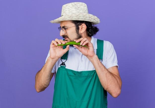 Jonge, bebaarde tuinman met een jumpsuit en een hoed met groene hete chilipeper die opzij kijkt en kronkelt over een blauwe achtergrond