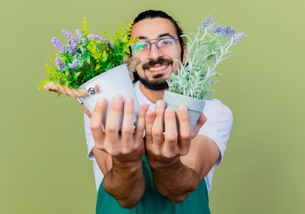 Jonge, bebaarde tuinmanmens die jumpsuit draagt die potplanten houdt die aan de voorkant glimlachen die vrolijk over de lichtgroene muur staat Gratis Foto