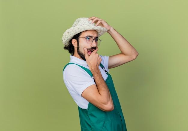 Jonge, bebaarde tuinmanmens die jumpsuit en hoed draagt die opzij kijkt, wordt verrast en verbaasd staande over de lichtgroene muur
