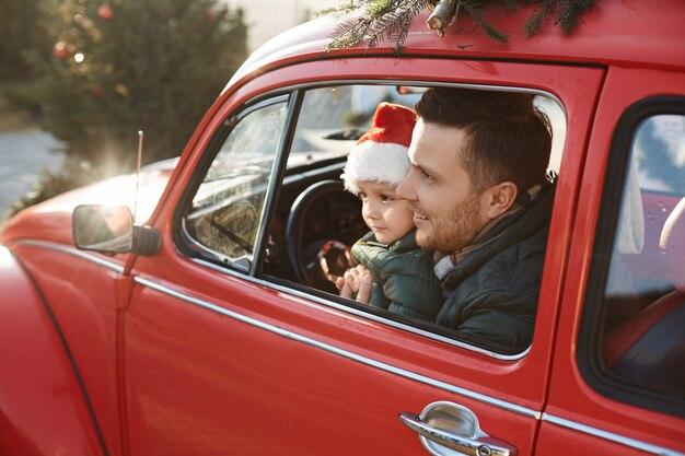 Jonge, bebaarde vader met schattige zoon in kerstman hoed poseren in de rode retro auto