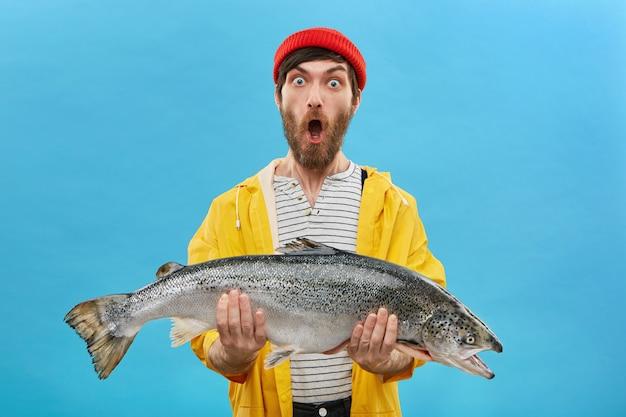 Jonge bebaarde visser die grote vers gevangen zeewatervis in beide handen houdt