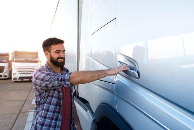 Jonge, bebaarde vrachtwagenchauffeur die de deur van het vrachtwagenvoertuig opent om de cabine binnen te gaan en te gaan rijden.