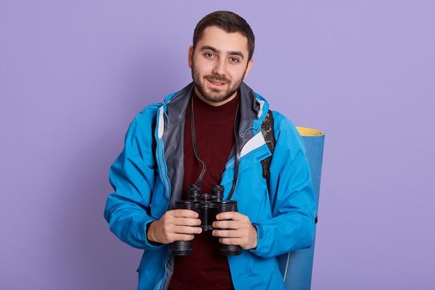 Jonge, bebaarde wandelaar met rugzak staan en camera kijken