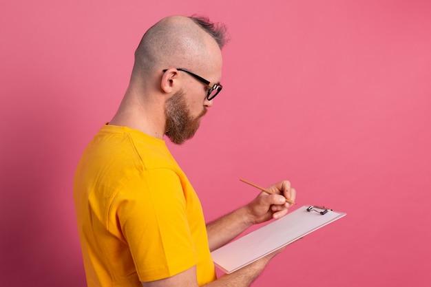 Jonge, bebaarde werknemer man vrijetijdskleding maken van aantekeningen tegen een roze achtergrond