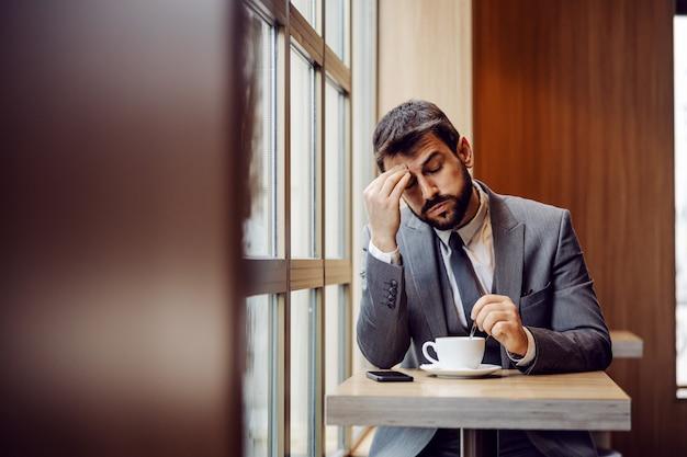 Jonge, bebaarde zakenman die in coffeeshop naast venster zit en hoofdpijn heeft. hij denkt dat koffie in de ochtend kan helpen.