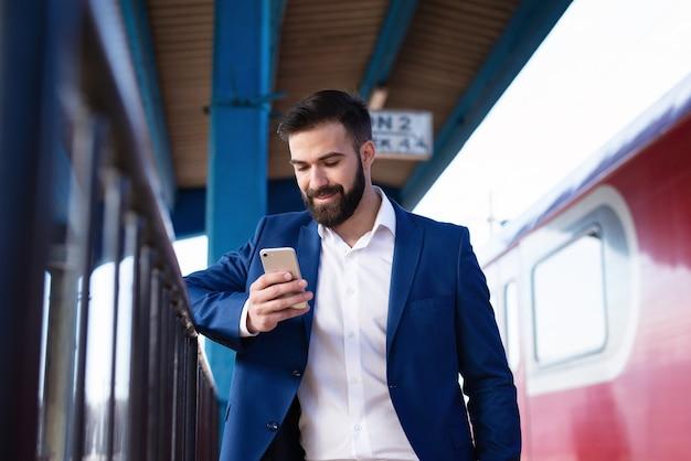 Jonge, bebaarde zakenman in elegant pak die op de metro wacht om aan het werk te gaan en zijn slimme telefoon gebruikt