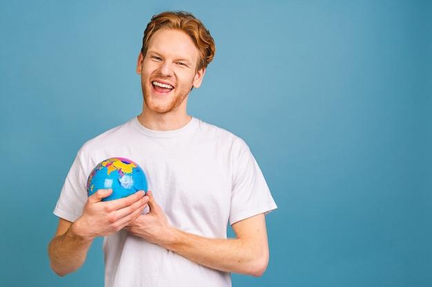 Jonge, bebaarde zakenman wil onbekende plaatsen verkennen, kijkt naar de wereldbol