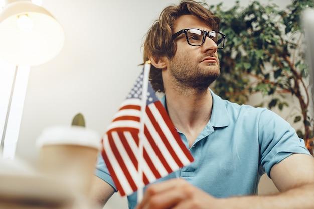 Jonge, bebaarde zakenman zittend aan tafel met laptop en amerikaanse vlag